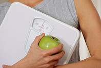 Dieting. Woman holding a weighing scale and an apple. Weight loss can be achieved through a balanced diet of healthy foods.