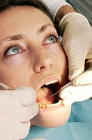 Dental examination. Dentist carrying out a dental examination on a woman. The dentist is using an angled mirror (right hand) to look at the patient´s ...