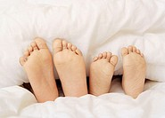 Children´s feet protruding from underneath a duvet. The feet belong to a five- year-old boy (left) and a four-year-old girl (right).