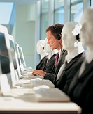 Businessman Working Between a Line of Dummies Wearing Headsets and Sitting in Front of Desks and PC´s