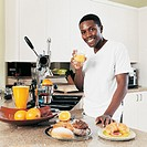Young Man Standing at a Kitchen Counter Holding a Glass of Orange Juice