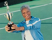 Portrait of a Mature Woman Standing on a Tennis Court Holding a Trophy
