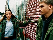 Teenage Boy and Girl With Attitude Stand in an Alley Leaning on a Roller Shutters