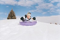 Young Boy Sledding Down a Snow-Covered Hill on a Rubber Ring