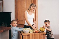 A Mother and her Children Preparing Vegetables in a Kitchen