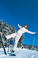 Smiling Woman Standing on One Leg on a Ski Slope