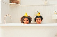 Portrait of Sisters in the Bath With Rubber Ducks on Their Heads