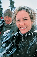 Portrait of a Mature, Smiling Couple Carrying Their Skis in the Snow