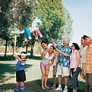 Family of Seven Watch Their Blindfolded Grandaughter Hitting a Pinata Hanging From a Tree
