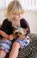 Three years old girl holding small dog, a pedigreed Yorkshire Terrier.