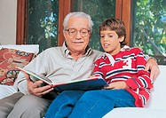 Grandfather Sitting Reading a Book With His Grandson