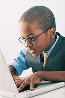 Young Boy Wearing Spectacles Using a Laptop