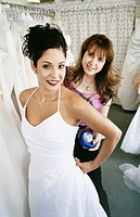 Bridal Shop Assistant Helping a Young Woman Try on Her Wedding Dress