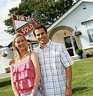 Couple Stand in Front of a Sold Sign on the Lawn of Their Bungalow