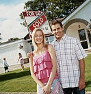 Couple Stand in Front of a Sold Sign on the Lawn of Their Bungalow With Their Son and Daughter Playing in the Background