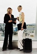 Two Businesswoman Reading from a Folder at an Airport
