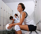 Female Volleyball Player Sits on a Bench in a Changing Room Holding a Volleyball, With Two of Her Team Mates Getting Ready in the Background