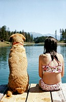 One Girl and her Pet Labrador Sitting on a Pier by a lake Looking at View