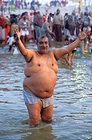 Fat man cheering in the Ganges river. Kumbh Mela festival. Allahabad, India
