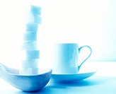 Wooden spoon with a tall stack of sugar cubes and a coffee cup