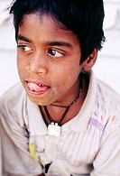 Young Indian boy with large eyes licking his upper lip looking away from the camera in thought