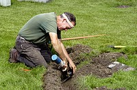 retired adult man working in second career installing lawn irrigation