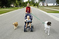Mother with 2 year son takes a walk with their 2 dogs