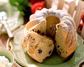 Gugelhupf with icing sugar and raisins, a piece    cut