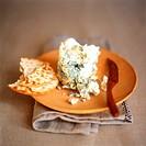 Stilton and cracker on wooden plate