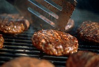 A Spatula Flipping a Hamburger on the Grill