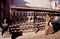 Nepalese woman spinning prayer wheels. Swayambhunath temple ('Monkey temple'). Kathmandu, Nepal