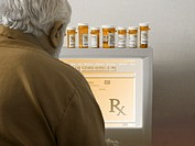 Photocomposite of an online pharmacy: a mature man ordering medication online.