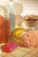 Close-up photograph of bath items: soap, a body scrubber, towels, potpourri, and bath oils.