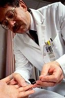Male doctor pricking a patient´s finger to draw blood for a cholesterol test.