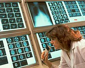 Female technician reviewing x-rays and recording her findings.
