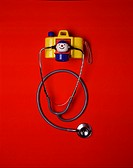 Still life of a stethoscope with a child´s colorful toy camera. The toy has a small smiling face figure, and the stethoscope is attached to the figure...