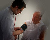 Male doctor examining the blood pressure of an elderly male patient.
