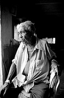 Black and white portrait of an elderly person looking sad and pensive.