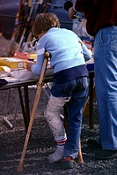 Boy with leg cast and crutches at a fair.