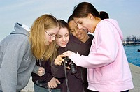 4 Four middle school aged females look at image on the back of a digital camera