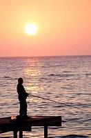 Fisherman on pier at sunset. Kusadasi. Turkey