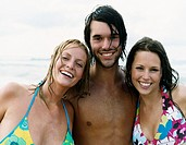 Portrait of a Young Man Standing Between Two Women Wearing Bikinis, His Arms Around Them