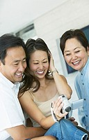 Young Woman Watches a Video on a Digital Camcorder With Her Husband and Mother, Laughing