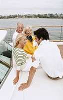 Mature Couple and Young Couple Sit Talking and Smiling on the Deck of a Sailboat