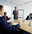 Business Manager Leading a Presentation Meeting in a Conference Room, Next a a Flip Chart