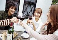Three Young Friends Around a Wooden Table Outside a Pub, Toasting Wine Glasses