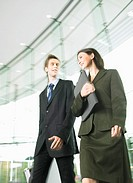 Businessman and Businesswoman Walk Side by Side From a Glass Door Walking Side by Side and Talking