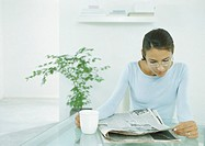 Woman sitting at table holding mug and looking at newspaper