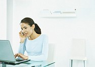 Woman sitting at table typing on laptop, holding cell phone to ear (thumbnail)