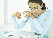 Woman holding mug looking down at newspaper